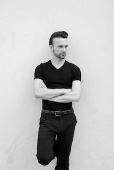 Black and white portrait of handsome italian man with arms crossed thinking