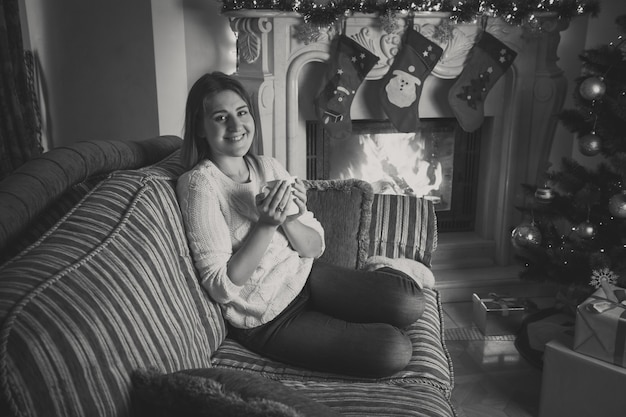 Black and white portrait of happy smiling woman drinking tea on sofa at fireplace decorated for christmas