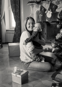 Black and white portrait of happy young mother hugging her 1 year old baby boy at christmas tree