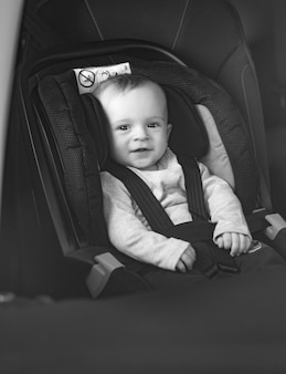 Black and white portrait of little baby boy sitting in car seat
