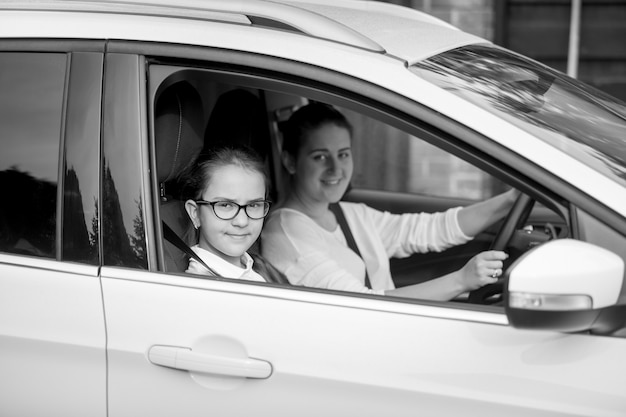 Black and white portrait of mother riding in car with teenage daughter