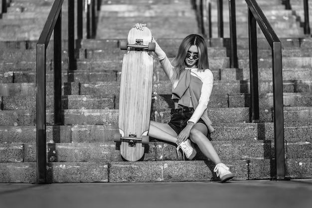 スケートボードに座っている若い女性の白黒の肖像画。高品質の写真
