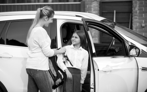 Black and white portrait of schoolgirl getting into the car and giving bag to mother