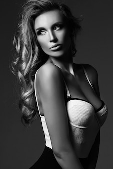 Black and white portrait of sensual glamour beautiful blond woman model lady with fresh makeup and healthy curly hair
