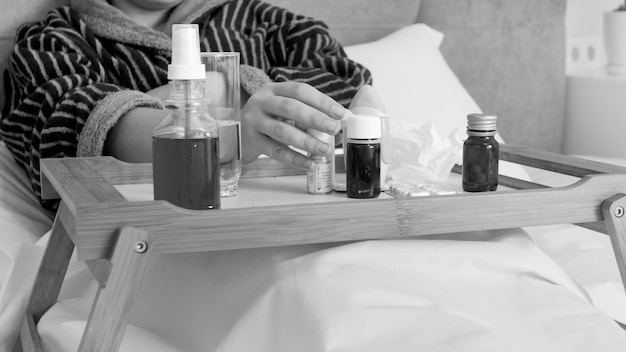 Black and white portrait of sick woman taking medicines fom wooden tray in bed.