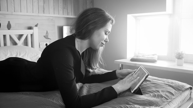 Black and white portrait of smiling businesswoman lying on bed and working on digital tablet computer