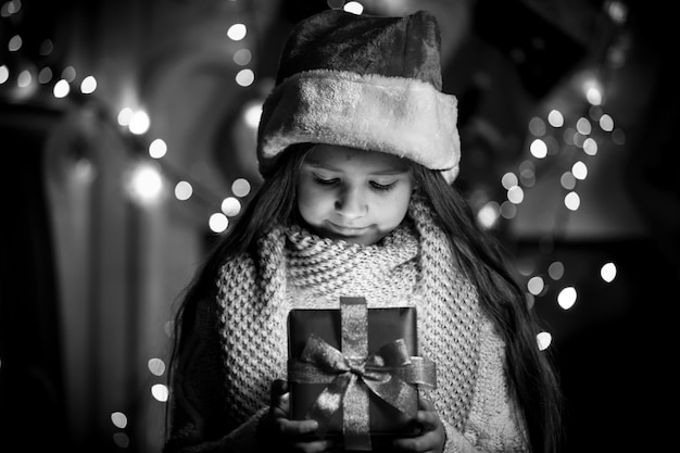 Black and white portrait of smiling girl opening christmas present box