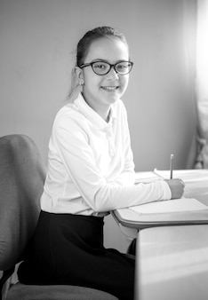 Black and white portrait of smiling schoolgirl posing behind table at classroom