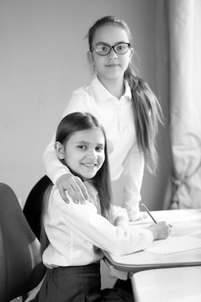 Black and white portrait of two happy schoolgirls doing homework at home