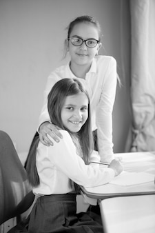 Black and white portrait of two happy schoolgirls posing at home