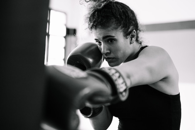 Black and white portrait of a woman boxer training punching gloves in a gym