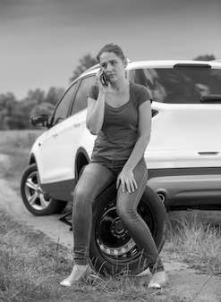 Black and white portrait of young female driver sitting next broken car and talking by phone