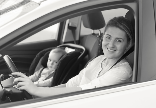 Black and white portrait of young mother driving car with her little baby on front seat