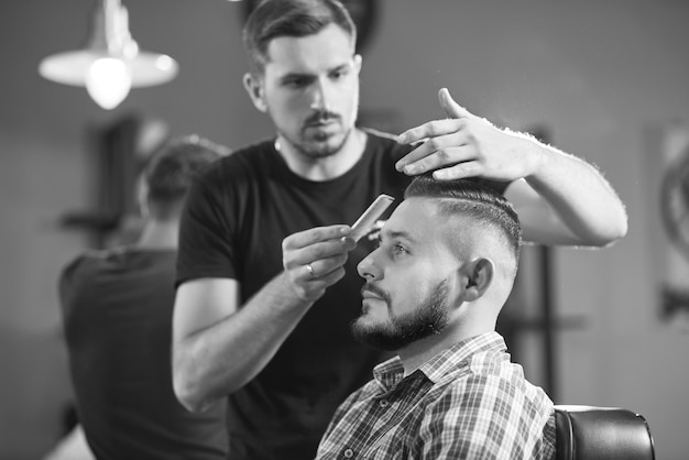 Black and white of a professional barber working cutting hair of his client with scissors
