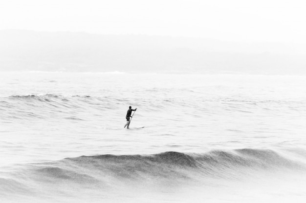 Black and white shot of a person in the middle of the sea