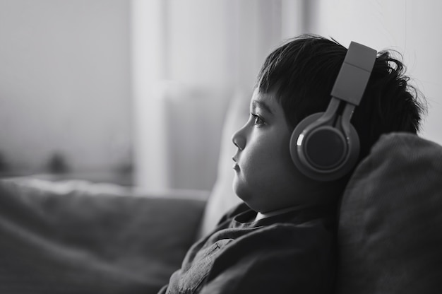 Black and white side view portrait child boy wearing headphones and looking out deep in thought, school boy in blue t-shirt listening to music,cute kid sitting on sofa relaxing in living room at home
