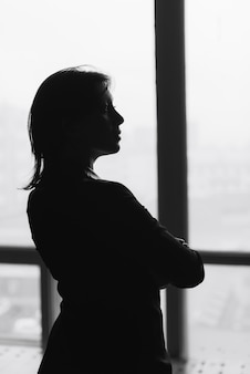 Black and white silhouette of a beautiful young woman at home