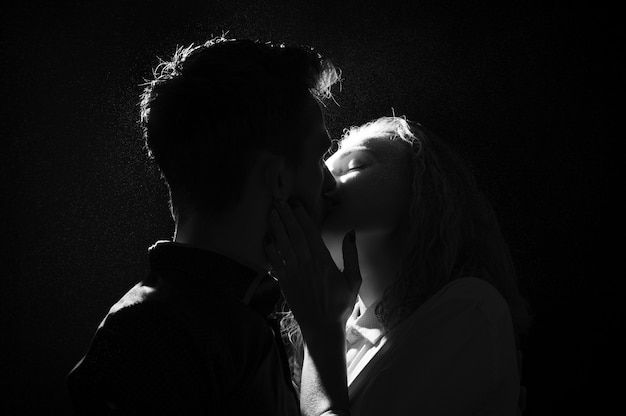 Black and white silhouette of a kissing couple