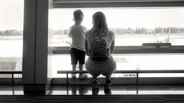 Black and white silhouette of young mother with little son standing at window in airport terminal.