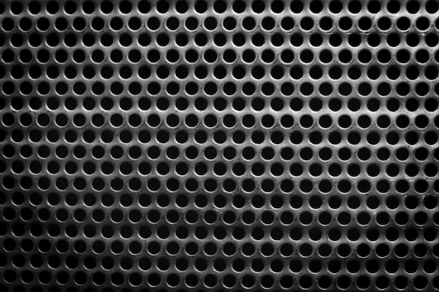 Black and white steel surface with little round holes
