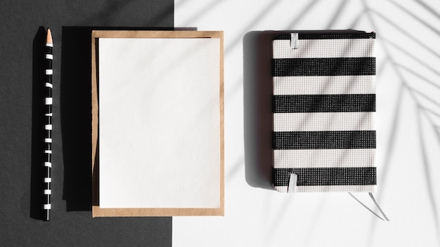Black and white striped notebook and white blanket with a black and white striped pencil  on a black and white background with a leaf shadow