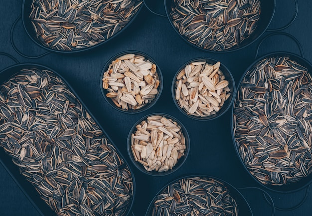 Black and white sunflower seeds in a bowls and plates on a black background. top view.