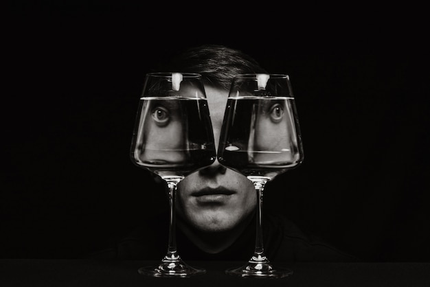 Black and white surreal portrait of a strange man looking through two glasses of water