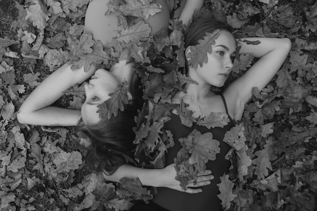 Black and white top portrait of two pretty tranquil women covered with leaves on ground