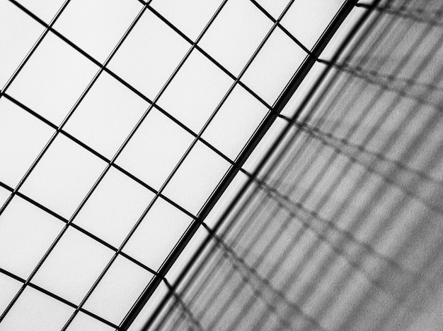 Black and white top view of a metal grid casting shadows