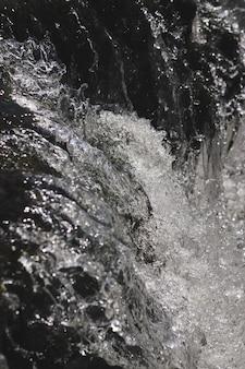 Colpo verticale in bianco e nero di spruzzi d'acqua