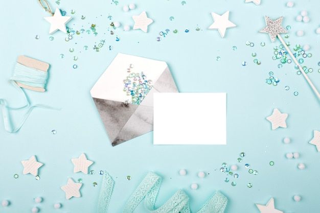 Black and white watercolor envelope  with empty card on blue background with stylish decoration stars and sequins. flat lay, top view