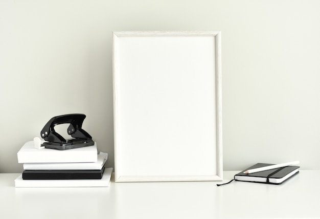 Black and white work space, blank photo frame, office supplies.