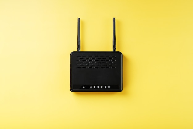 여유 공간이있는 노란색 배경에 검은 색 wi-fi 라우터.