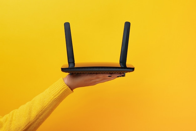 Black wifi router held in hand isolated