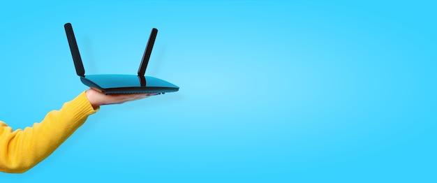 Черный маршрутизатор wi-fi под рукой над синим