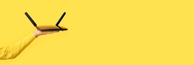 노란색 위에 손에 검은 wifi 라우터