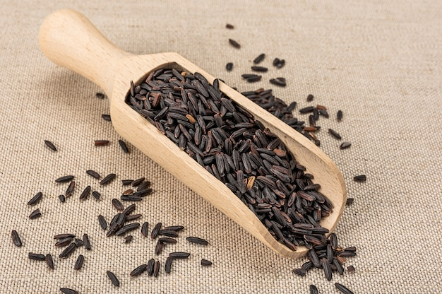검은 야생 쌀. 유기농 검은 야생 쌀과 나무 국자 숟가락. 나무로되는 숟가락에 생 쌀된, 원시, 검은 야생 쌀 곡물의 힙