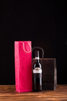 Black wine bottle  with beautiful paper bag over wooden table
