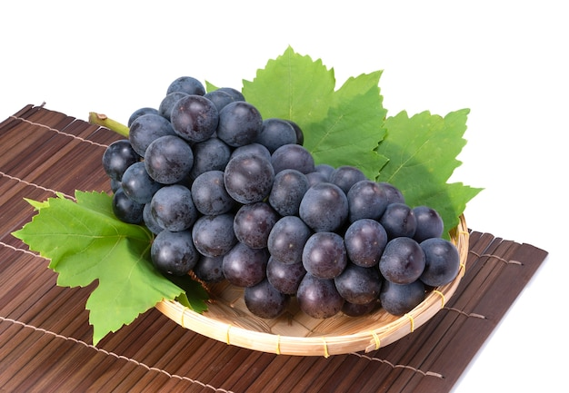 Black wine grape with leaves or kyoho grape in bamboo basket on wooden table in garden,