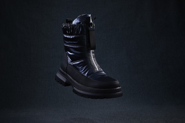 Black winter walking shoes levitate in air. modern stylish female shoes for off-road walking.