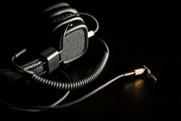 Black wired on ear headphones with gold headphone jack on dark background