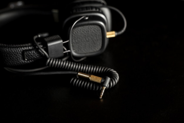 Black wired on ear headphones with gold headphone jack