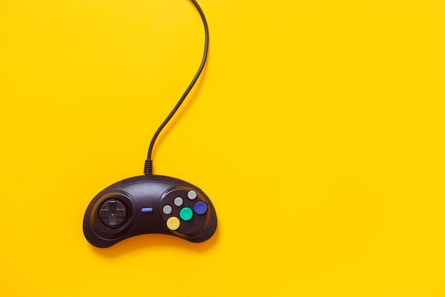 黄色で隔離される黒い有線ゲームパッド。コンソールゲームのコンセプト