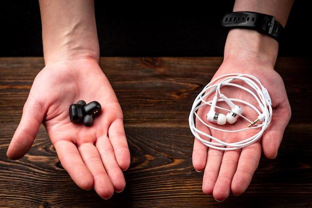 暗い木製の背景に黒のワイヤレスと白の有線ヘッドフォン。