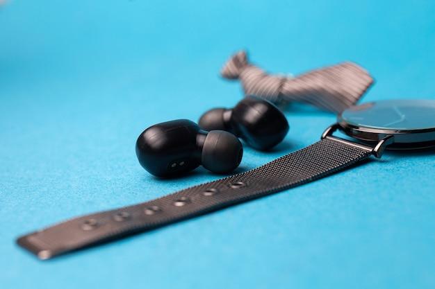 黒のワイヤレスヘッドフォンと青い背景の時計