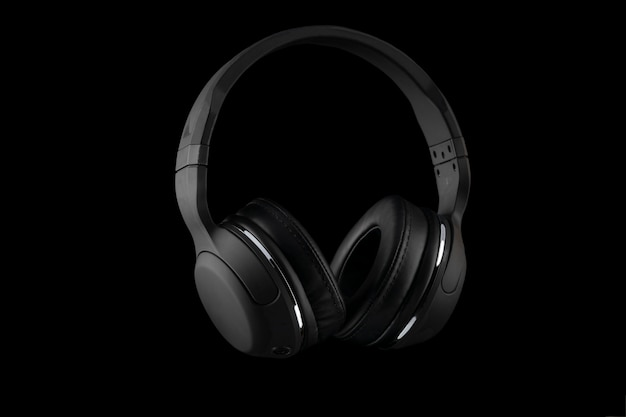 Black wireless headphones isolated on a black background.
