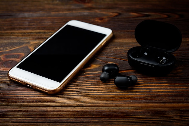 Black wireless headphones and mobile phone on dark wooden background.