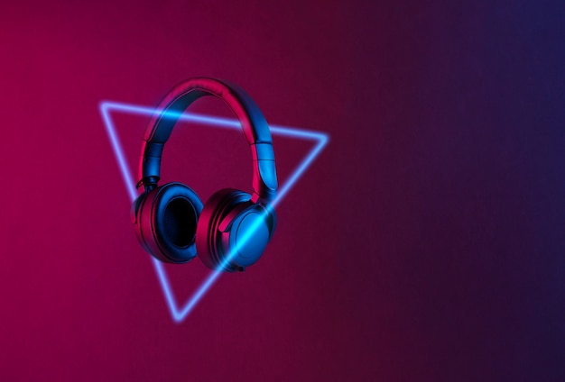 Black wireless headphones and neon triangle lit with colorful light floating on abstract background with copy space