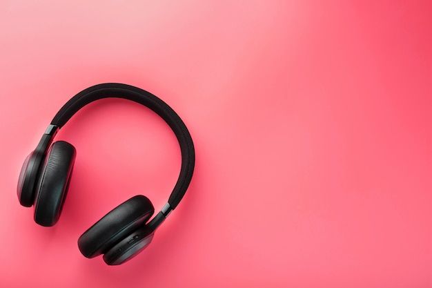Black wireless headphones on pink