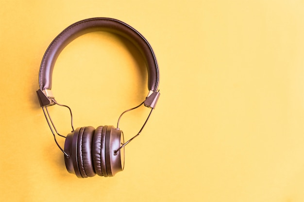 Black wireless headphones on a yellow background, top view, copyspace